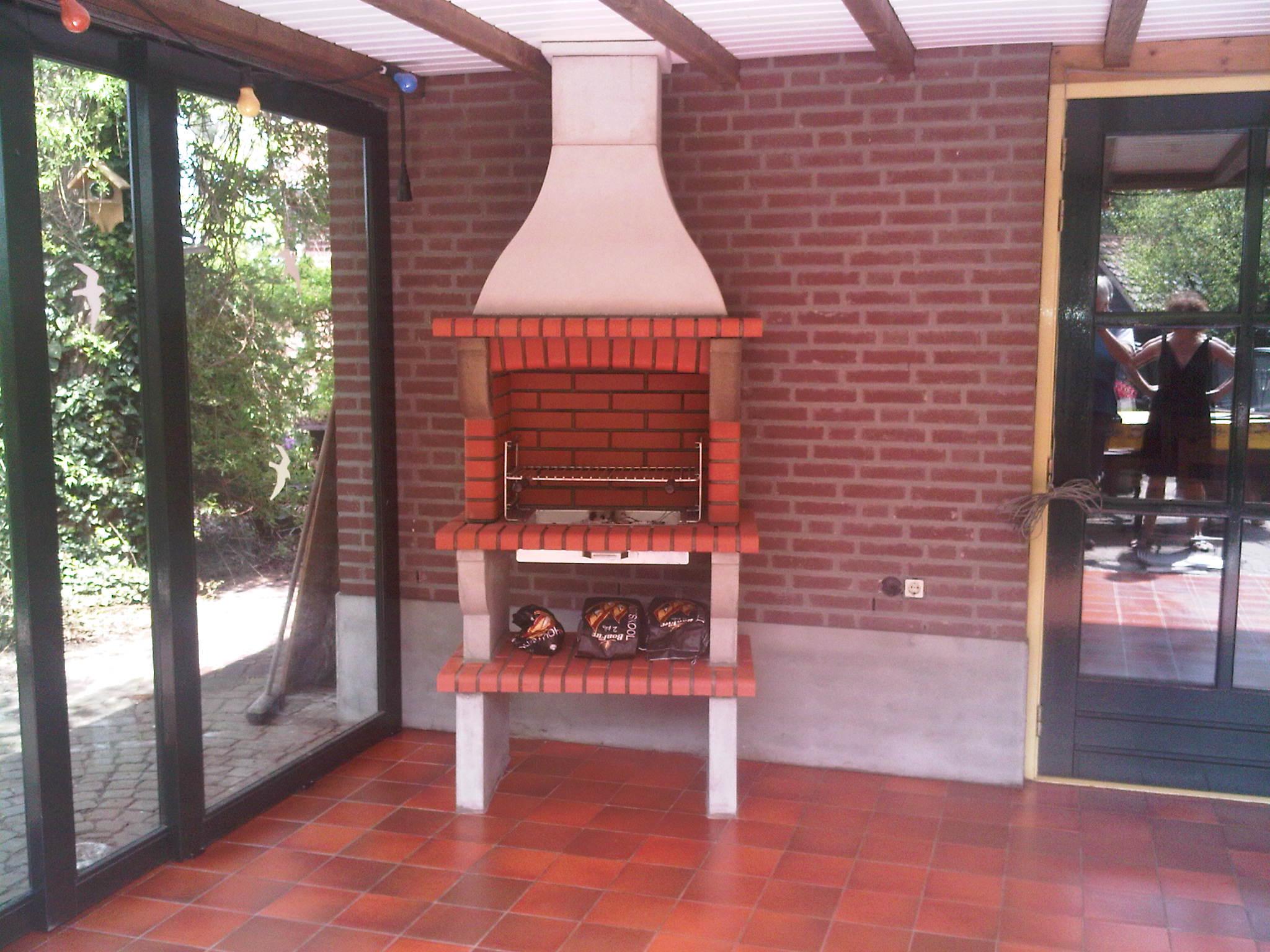 Evora 02, steen kleur Rood, met grillset G14 RvS inbouw. haard is in serre geplaasts, rookkanaal middels pijp door dak.